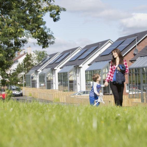 A woman and a little boy walk through the grass next to a housing development