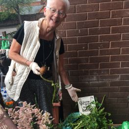 Mary shows her vegetables she has grown in the community garden