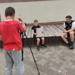 Three boys learn to film and present during workshops