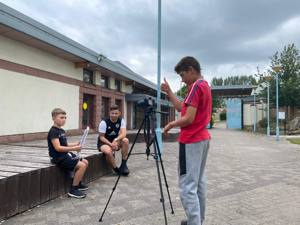 Two boys are shooting a video as part of a workshop, with one filming and the other presenting.